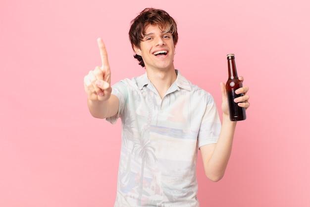 Junger tourist mit einem bier, das stolz und zuversichtlich lächelt und nummer eins macht