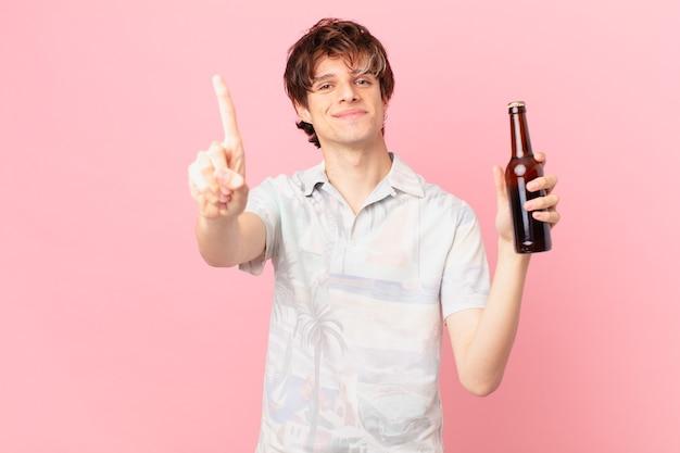 Junger tourist mit einem lächelnden und freundlich aussehenden bier, das nummer eins zeigt