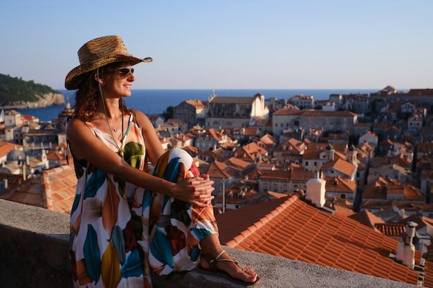 Junger tourist mit hut und gläsern bei sonnenuntergang in der alten stadt dubrovnik, kroatien