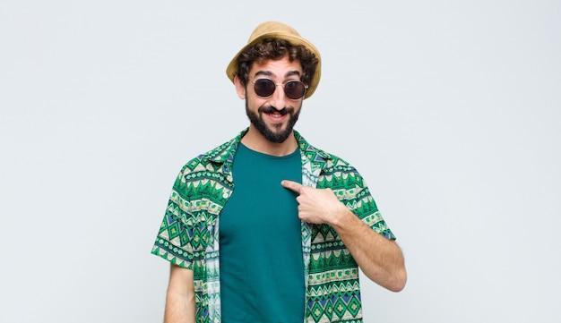 Junger touristenmann, der glücklich, stolz und überrascht aussieht, fröhlich auf sich selbst zeigt, sich sicher und hoch über weißer wand fühlt