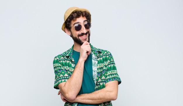 Junger touristenmann, der mit einem glücklichen, selbstbewussten ausdruck mit der hand am kinn lächelt, sich wundert und zur seite gegen weiße wand schaut