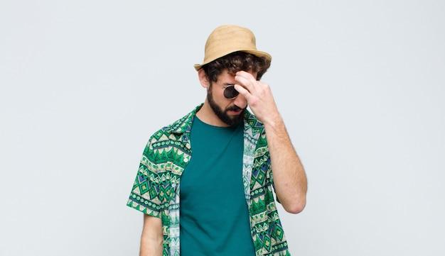 Junger touristenmann, der sich gestresst, unglücklich und frustriert fühlt, stirn berührt und migräne von starken kopfschmerzen über weißer wand leidet