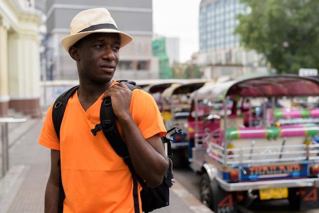 Junger touristenmann, der während des haltens des rucksacks und der besichtigung am bahnhof mit dreiradparken in bangkok thailand denkt