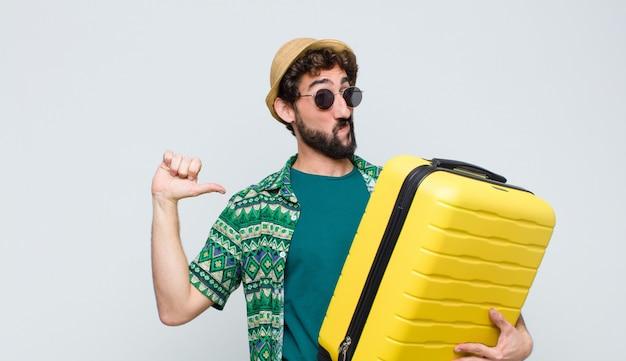 Junger touristenmann mit einem koffer gegen weiße wand. reisekonzept