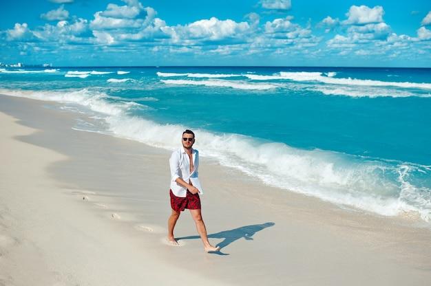 Junger touristischer mann, der allein auf dem mexiko-reisekonzept des strandes von cancun spaziert