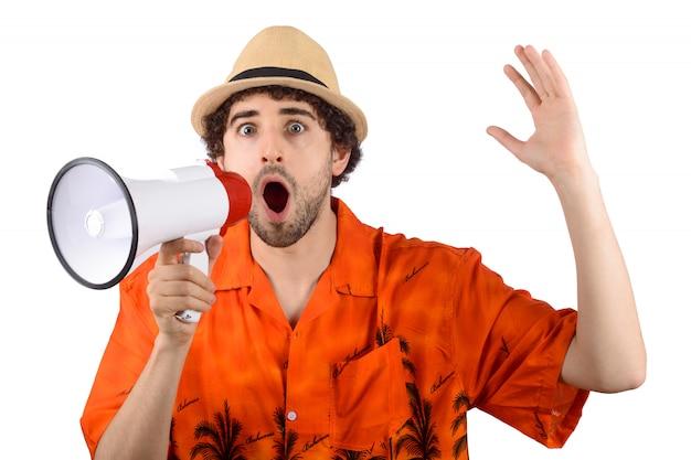 Junger touristischer mann, der auf einem megaphon schreit.