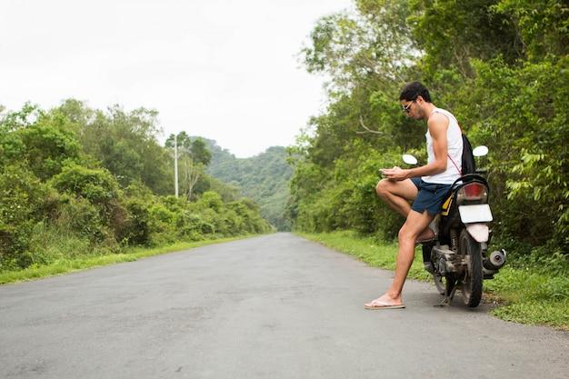 Junger touristischer reiter, der auf einem mietmotorrad unter verwendung eines smartphone mitten in einer straße sitzt