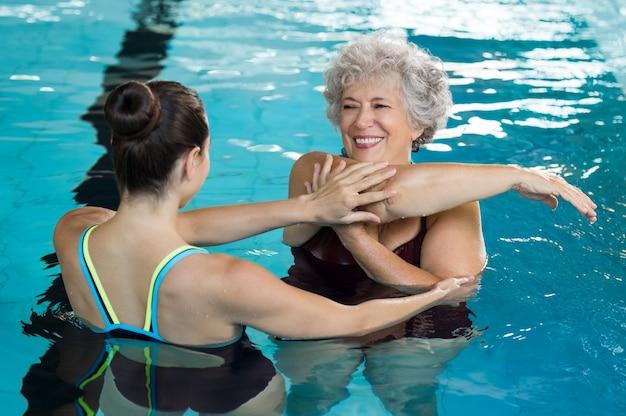Junger trainer, der ältere frau in der aqua-aerobic hilft