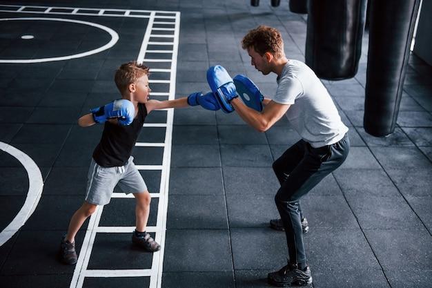 Junger trainer unterrichtet kinderboxsport im fitnessstudio.