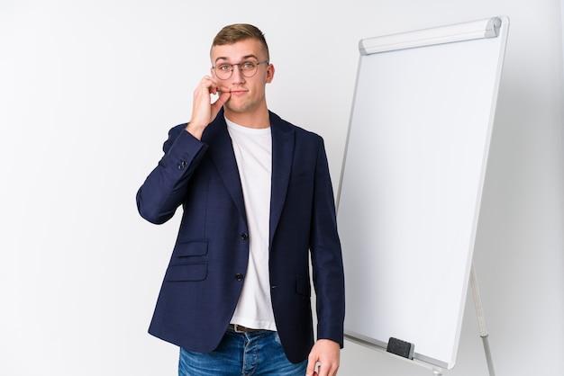 Junger trainermann, der ein weißes brett mit den fingern auf den lippen halten ein geheimnis zeigt.