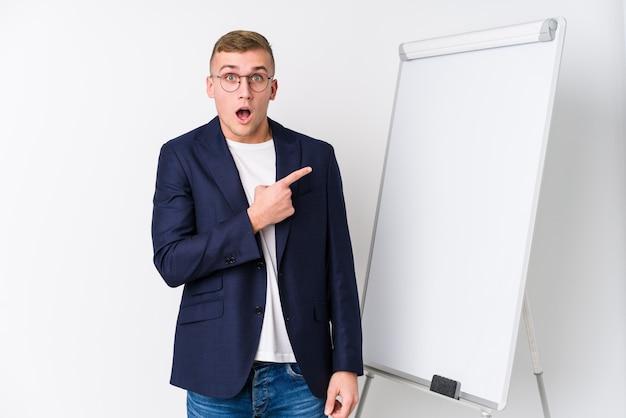 Junger trainermann, der ein weißes brett zeigt auf die seite zeigt