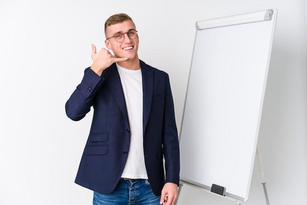 Junger trainermann, der ein weißes brett zeigt eine handyanrufgeste mit den fingern zeigt.