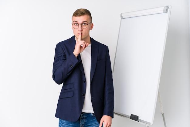 Junger trainermann, der eine weiße tafel zeigt, die ein geheimnis hält oder um stille bittet.