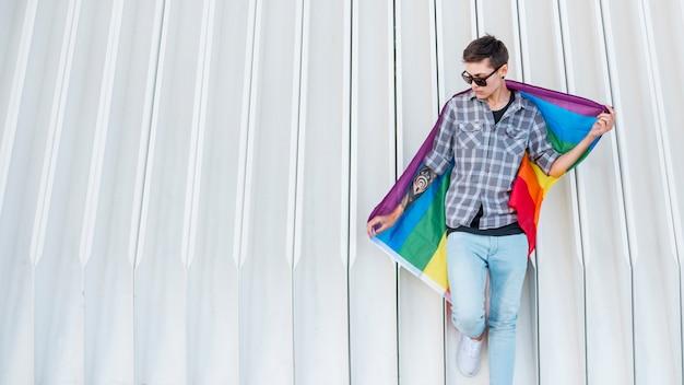 Junger transgender, der lgbt-flagge hält