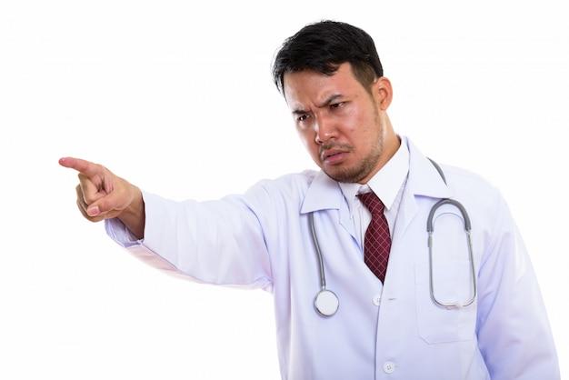 Junger trauriger asiatischer mannarzt, der auf entfernung zeigt