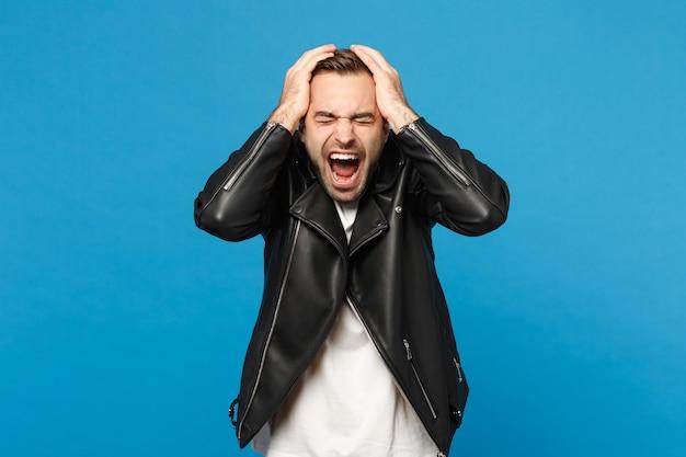 Junger trauriger frustrierter besorgter unrasierter mann in der schwarzen jacke, dem weißen t-shirt, das kamera einzeln auf blauem wandhintergrundstudioporträt schaut. menschen aufrichtige emotionen lifestyle-konzept. kopieren sie platz.