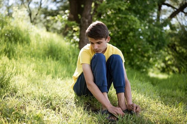 Junger trauriger kerl, der auf dem gras allein im wald während des tages sitzt