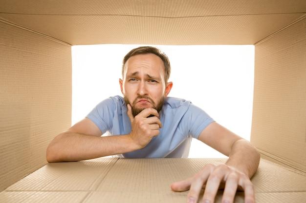 Junger trauriger mann, der das größte postpaket lokalisiert auf weiß öffnet. enttäuschtes männliches model oben auf dem karton, der nach innen schaut.