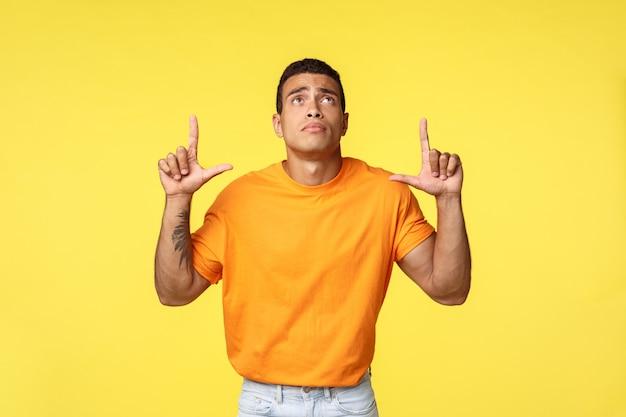 Junger trauriger mann mit tätowiertem arm im orangefarbenen t-shirt, hose, einsam mit traurigkeit und bedauern aufblickend, nach oben zeigend, verpasste guten verkauf, eifersüchtig auf etwas, stehend