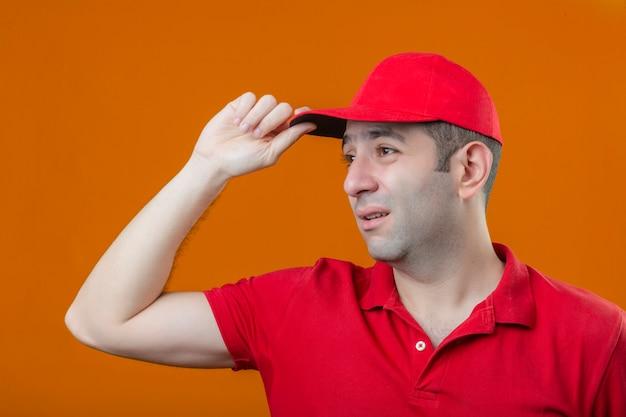 Junger trauriger verärgerter lieferbote im roten poloshirt und in der kappe, die ich über lokalisiertem orangefarbenem hintergrund beiseite schauen