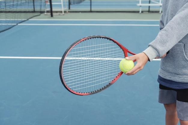 Junger tweenjungen-tennisspieler auf blauem gericht im freien