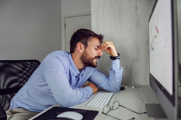 Junger überarbeiteter geschäftsmann, der in seinem büro sitzt und den kopf hält, weil er einen großen fehler gemacht hat. er hat auch kopfschmerzen.