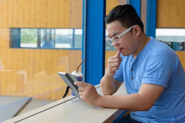Junger übergewichtiger asiatischer nerdmann, der beim lesen des buches am coffeeshop denkt