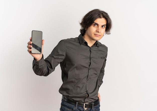 Junger überraschender hübscher kaukasischer mann hält telefon, das kamera betrachtet, lokalisiert auf weißem hintergrund mit kopienraum