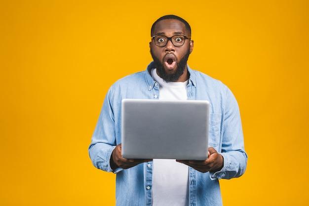Junger überraschter afrikanischer mann, der steht und laptop-computer benutzt