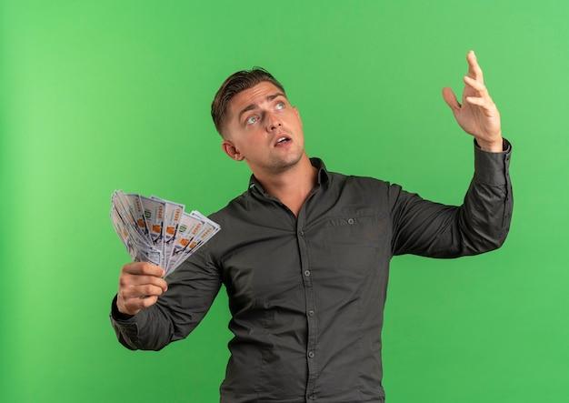 Junger überraschter blonder gutaussehender mann hält geld mit erhabener hand, die lokal auf grünfläche mit kopienraum nach oben schaut
