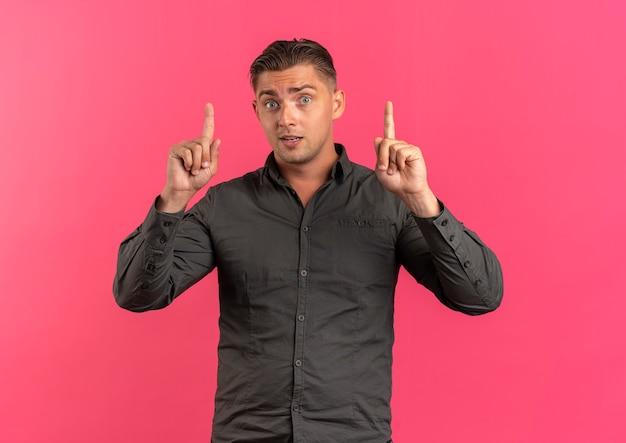 Junger überraschter blonder gutaussehender mann zeigt isoliert auf rosa raum mit kopienraum
