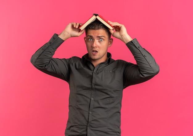 Junger überraschter blonder hübscher mann hält buch über kopf lokalisiert auf rosa raum mit kopienraum