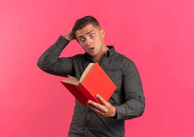 Junger überraschter blonder hübscher mann hält kopf und betrachtet buch lokalisiert auf rosa hintergrund mit kopienraum