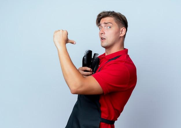 Junger überraschter blonder männlicher friseur in uniform hält und zeigt auf friseurwerkzeuge