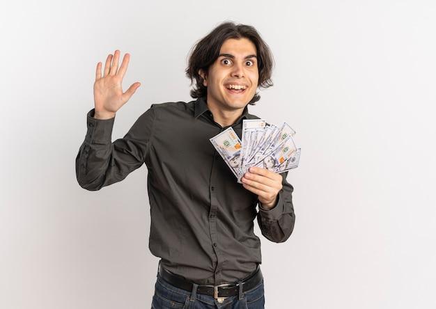 Junger überraschter gutaussehender kaukasischer mann hält geld und hebt hand