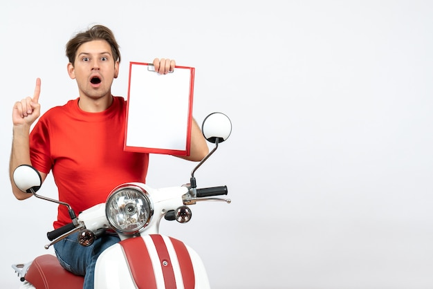 Junger überraschter kuriermann in der roten uniform, die auf roller sitzt, dokumente hält und auf gelbe wand zeigt