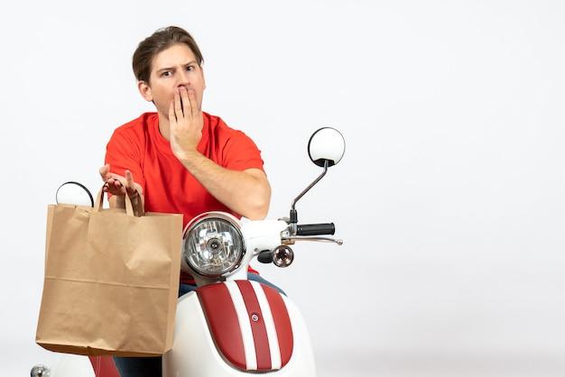 Junger überraschter lieferbote in der roten uniform, die auf roller sitzt, der papiertüte auf weißer wand hält
