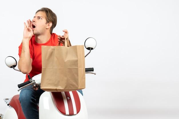 Junger überraschter lieferbote in der roten uniform, die auf roller sitzt, papiertüte hält und jemanden auf weißer wand anruft