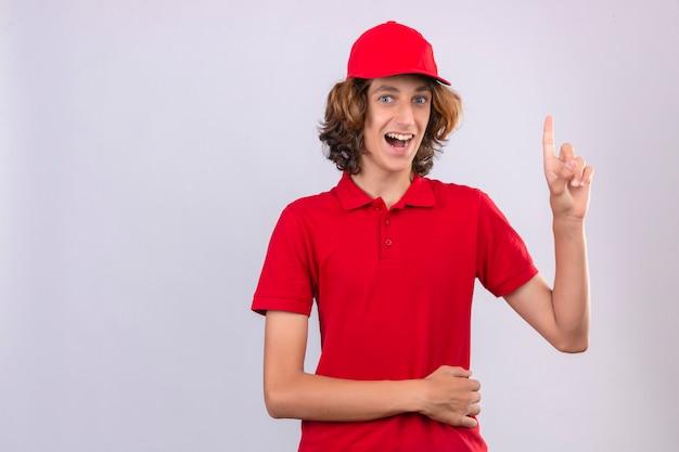 Junger überraschter lieferbote in der roten uniform, die eine große idee anzeigt, die mit glücklichem gesicht über lokalisiertem hintergrund lächelt