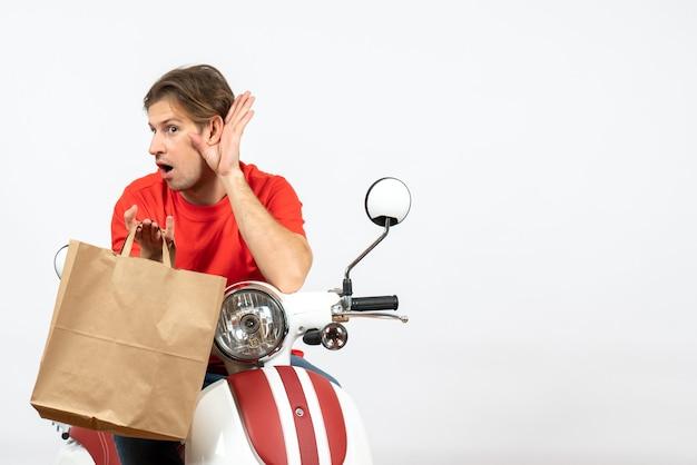 Junger überraschter lieferbote in roter uniform, der auf roller sitzt, papiertüte hält und dem letzten klatschen auf weißer wand lauscht
