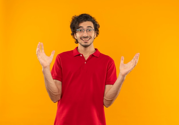 Junger überraschter mann im roten hemd mit optischer brille hält hände offen lokalisiert auf orange wand