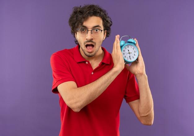 Junger überraschter mann im roten hemd mit optischer brille hält uhr mit beiden zeigern und sieht auf violetter wand isoliert aus