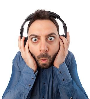 Junger überraschter mann mit kopfhörern