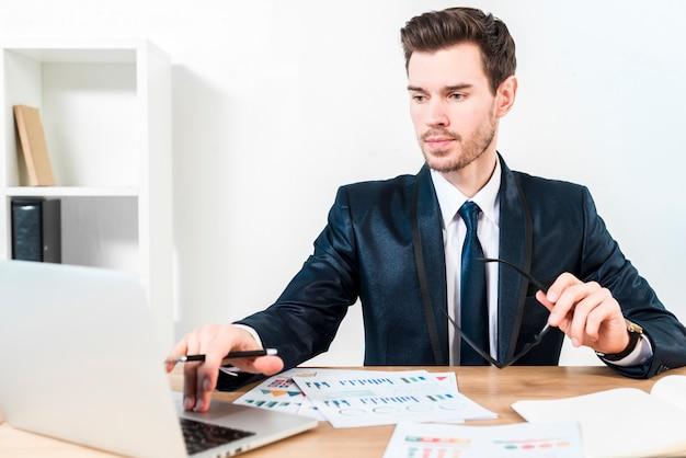 Junger überzeugter geschäftsmann unter verwendung des laptops am arbeitsplatz im büro