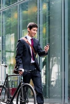 Junger überzeugter mann, der am handy nach dem fahrradkommutin spricht