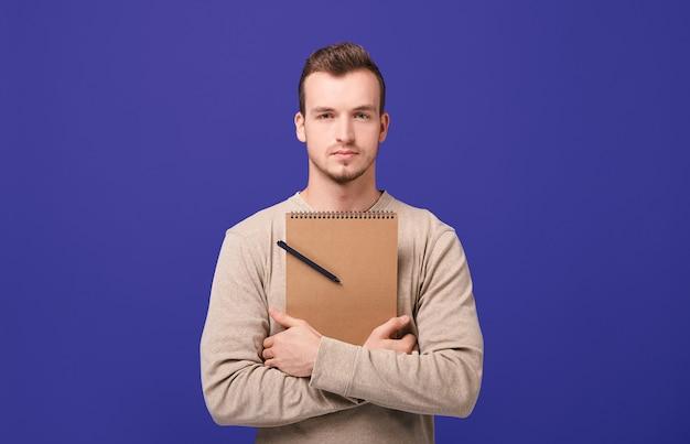 Junger überzeugter überzeugter kerl, der ein braunes notizbuch mit schwarzem kugelschreiber durch hände umarmt