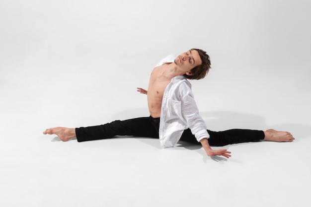 Junger und anmutiger balletttänzer im minimalen schwarzen stil lokalisiert auf weiß