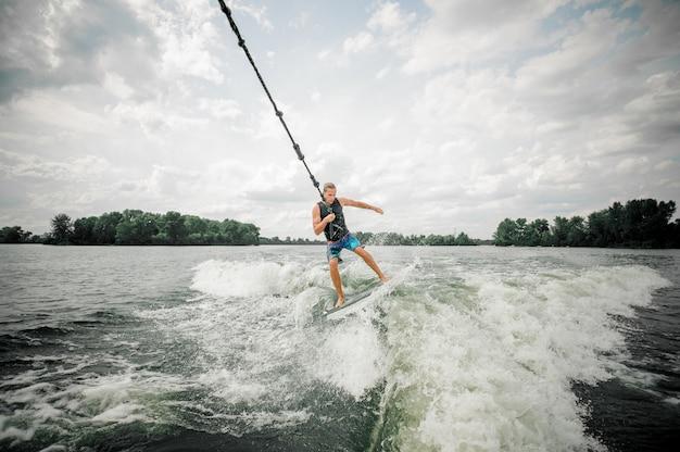 Junger und athletischer mann, der auf dem brett hält ein kabel wakesurfing ist