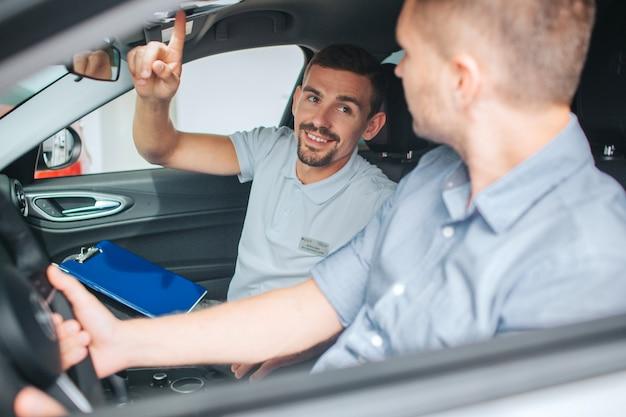 Junger und bärtiger berater sitzen im auto