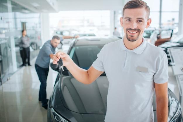Junger und bärtiger berater steht und hält schlüssel vom schwarzen auto. er schaut auf caera und lächelt. kerl trägt weißes hemd. potenzieller käufer ist in der nähe. er schaut ins auto.